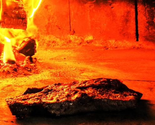 Una peça de carn coent-se al forn de llenya del Restaurant Ibèric d'Ullastret